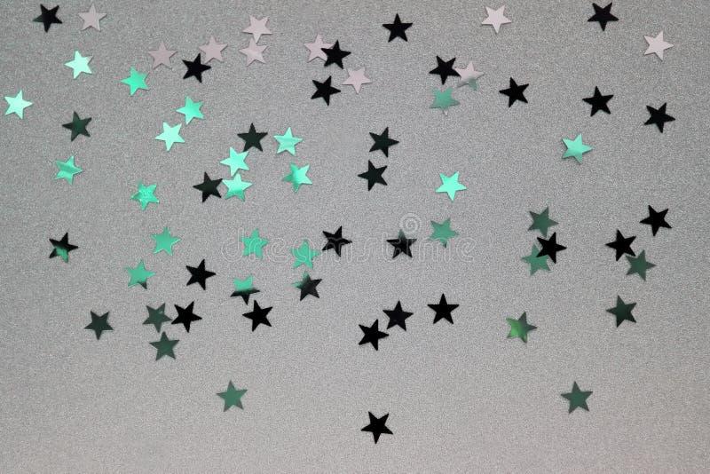 El confeti asteroide asperjó en un fondo de plata del brocado fotografía de archivo libre de regalías