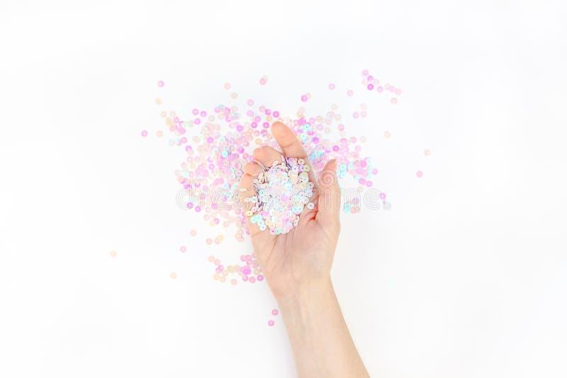 El confeti en colores pastel de la perla chispea con la mano de la mujer fotografía de archivo libre de regalías