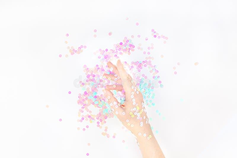 El confeti en colores pastel de la perla chispea con la mano de la mujer fotos de archivo