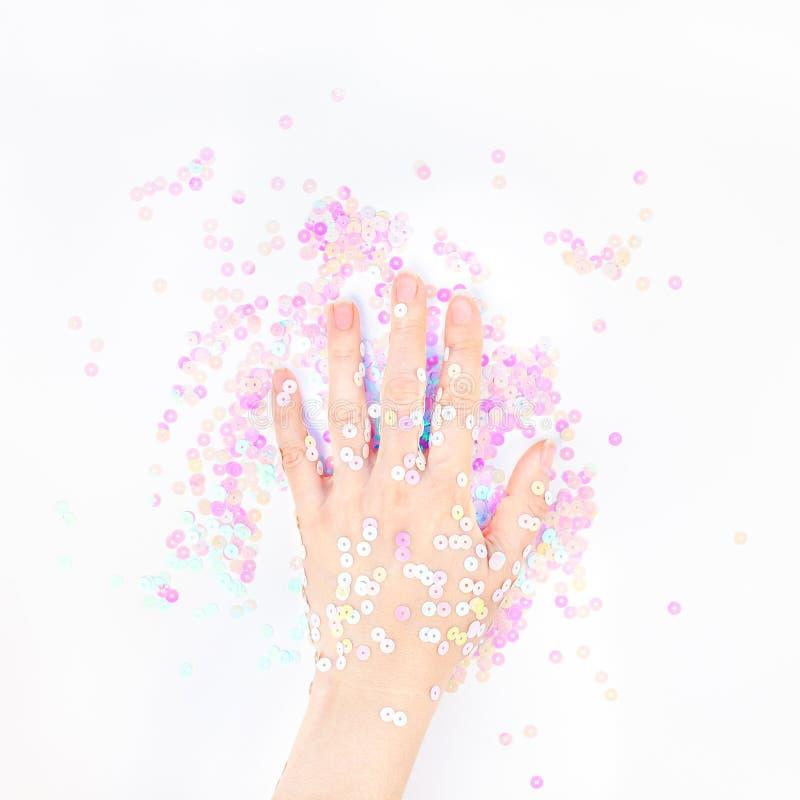 El confeti en colores pastel de la perla chispea con la mano de la mujer fotografía de archivo