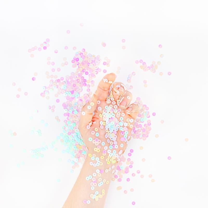 El confeti en colores pastel de la perla chispea con la mano de la mujer imágenes de archivo libres de regalías