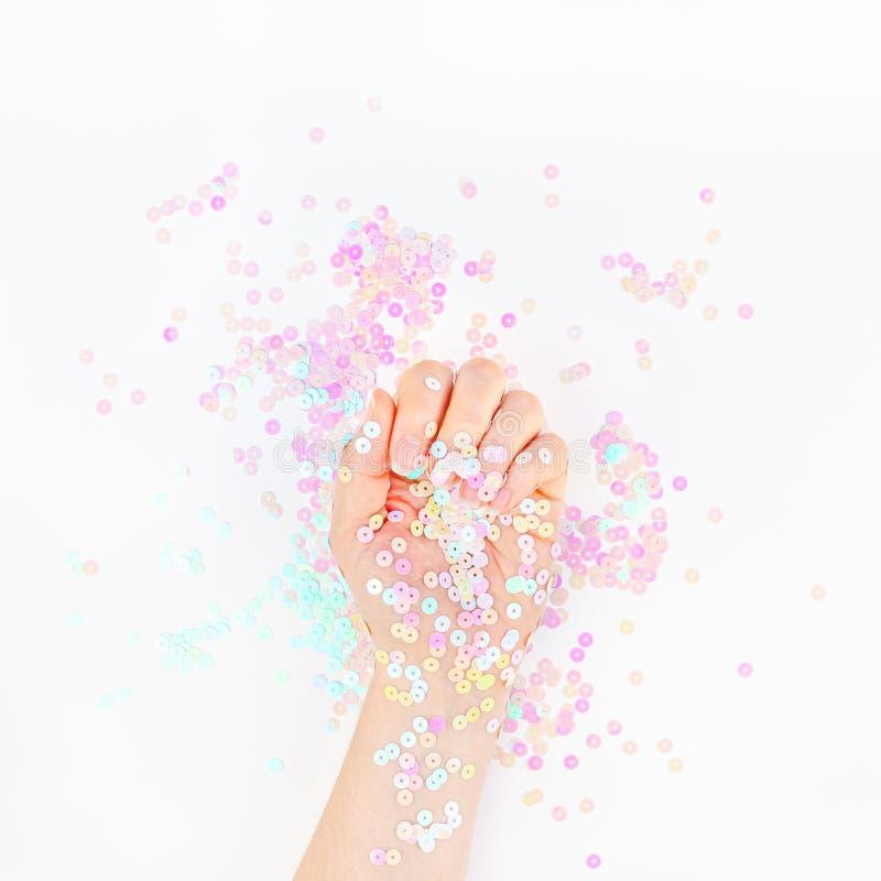 El confeti en colores pastel de la perla chispea con la mano de la mujer foto de archivo