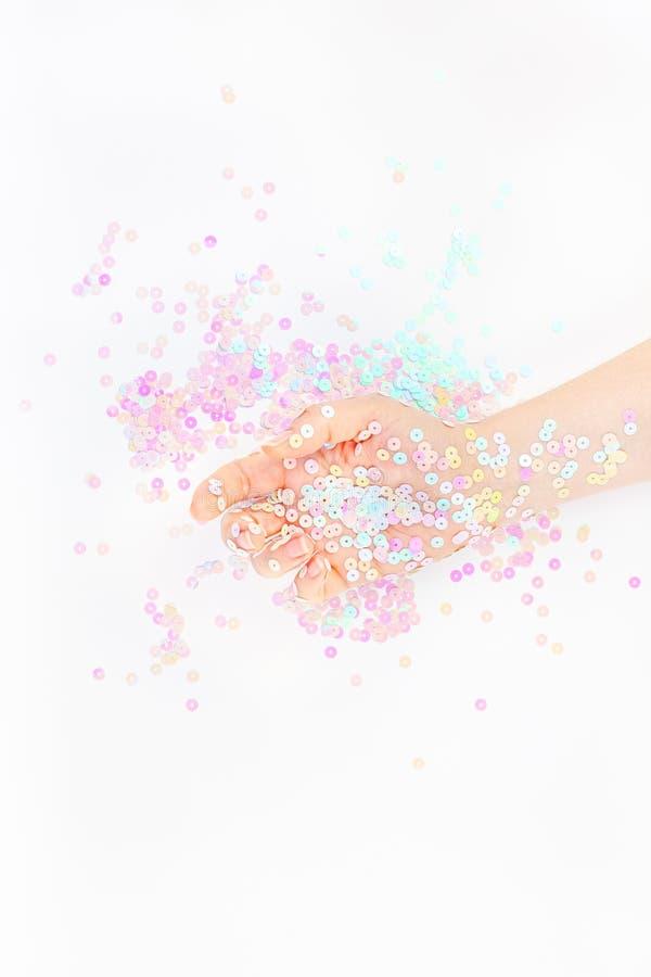 El confeti en colores pastel de la perla chispea con la mano de la mujer imagen de archivo libre de regalías
