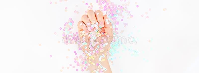 El confeti en colores pastel de la perla chispea con la mano de la mujer foto de archivo libre de regalías