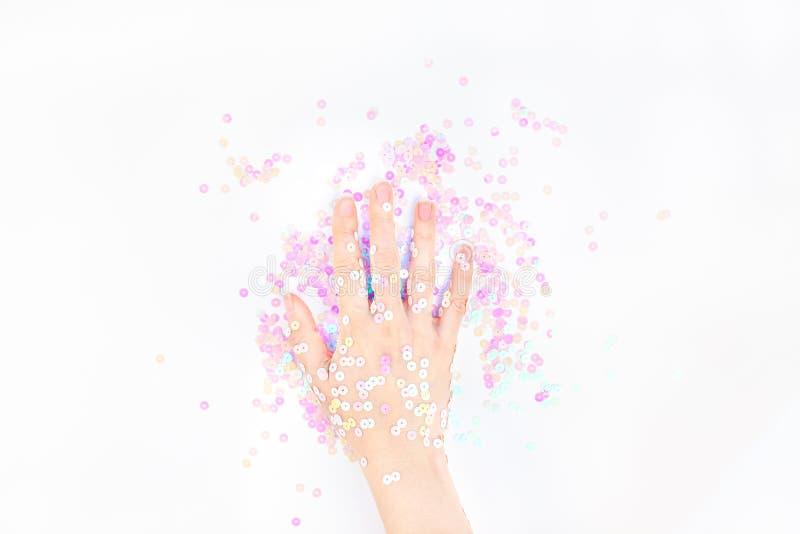 El confeti en colores pastel de la perla chispea con la mano de la mujer imagenes de archivo