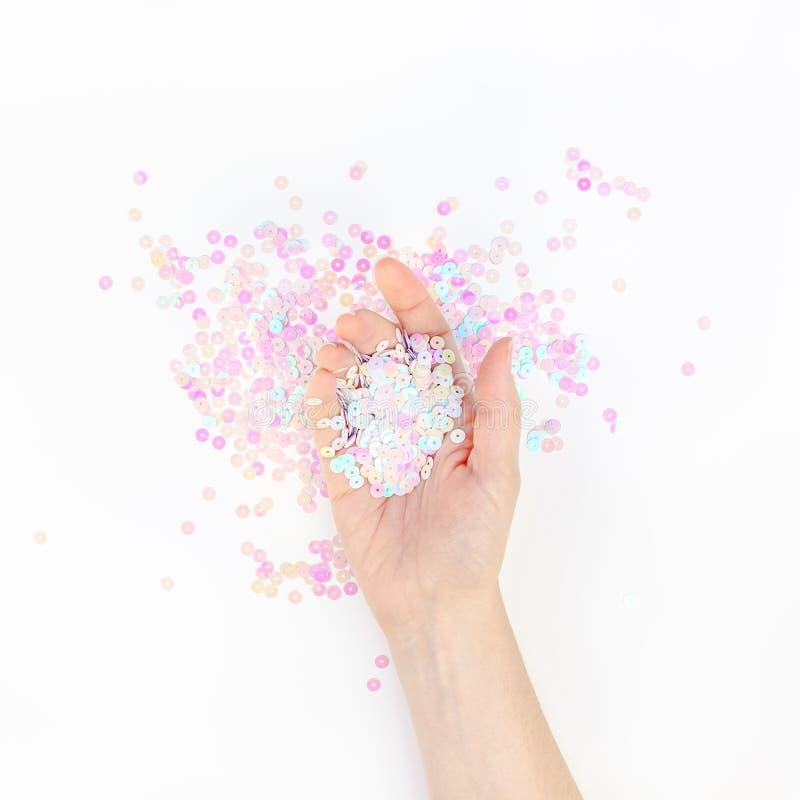 El confeti en colores pastel de la perla chispea con la mano de la mujer imagen de archivo