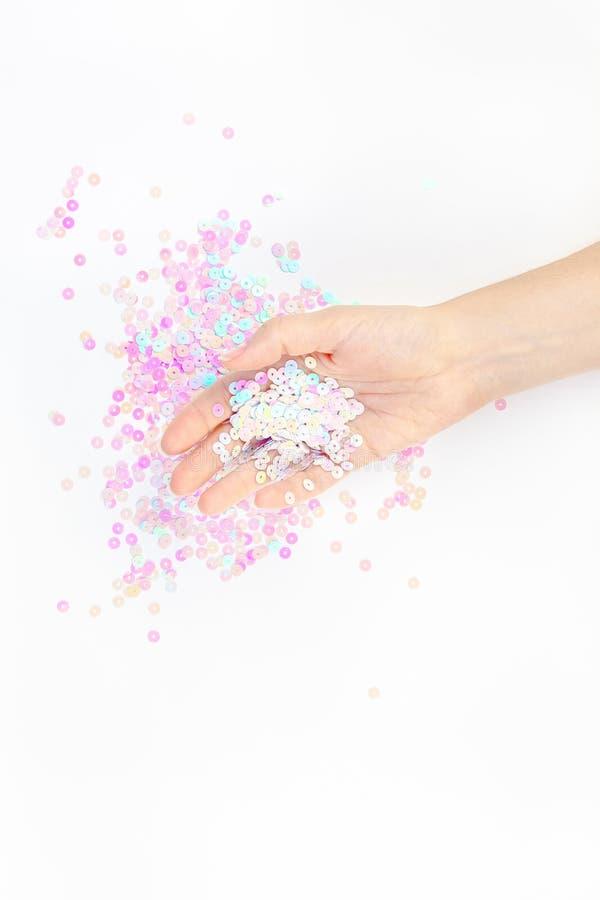 El confeti en colores pastel de la perla chispea con la mano de la mujer fotos de archivo libres de regalías
