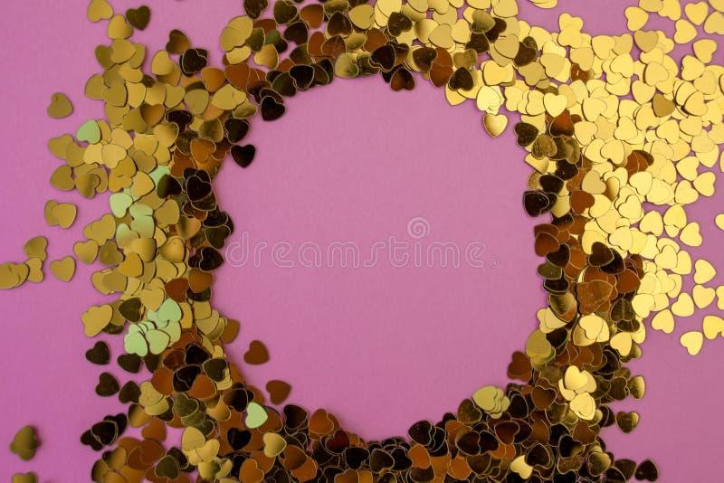 El confeti en forma de coraz?n dispers? en un fondo rosado Celebraci?n y partido, concepto Copie el espacio fotos de archivo libres de regalías