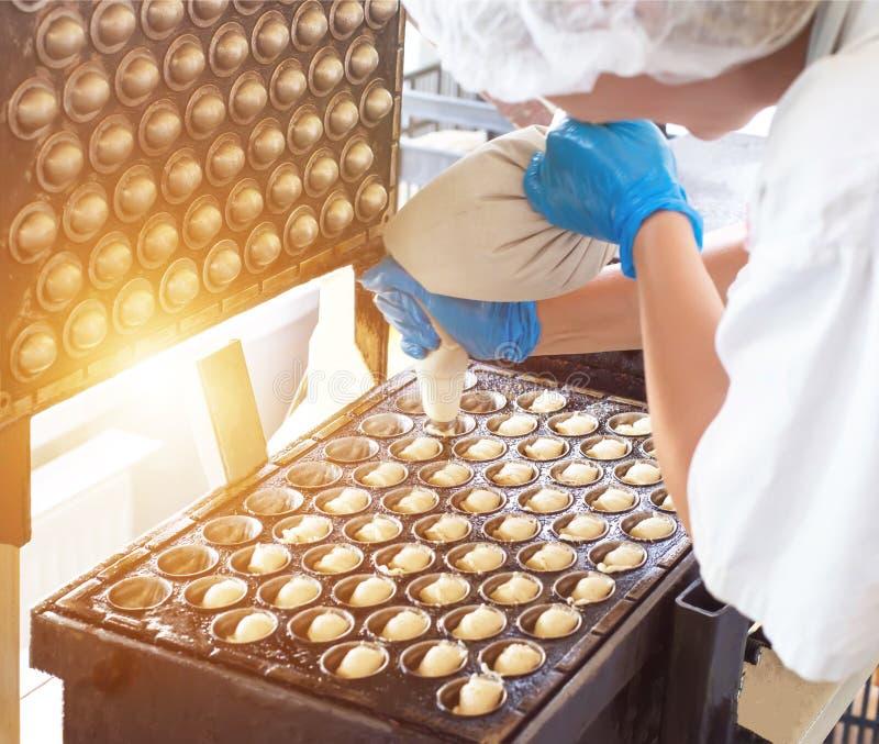El confitero de sexo femenino fija la pasta en la forma que cuece de nueces con leche condensada Producción de la confitería, hec foto de archivo