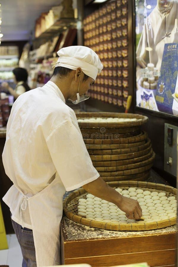 El confitero fabrica las galletas en tienda de chucherías foto de archivo libre de regalías