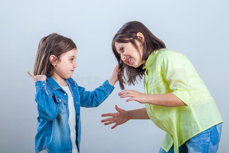 El conflicto entre las hermanas, una hermana más joven tira del pelo un si más viejo fotos de archivo