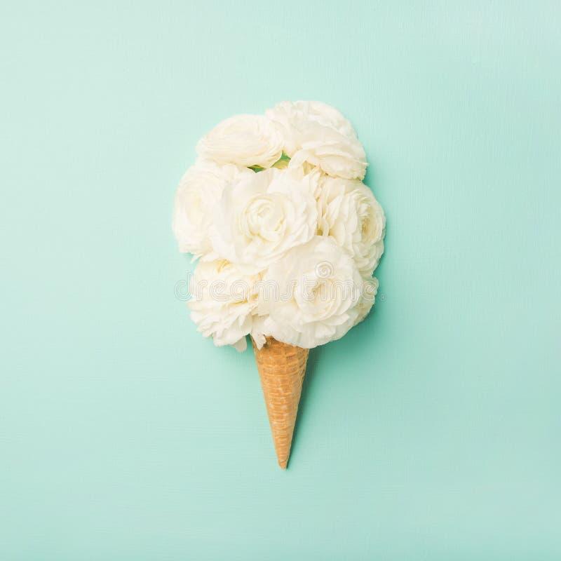 El cono de la galleta con el ranúnculo blanco florece sobre fondo en colores pastel azul fotografía de archivo