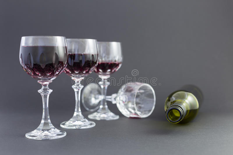 El conseguir bebido del vino rojo en cristales elegantes imagenes de archivo