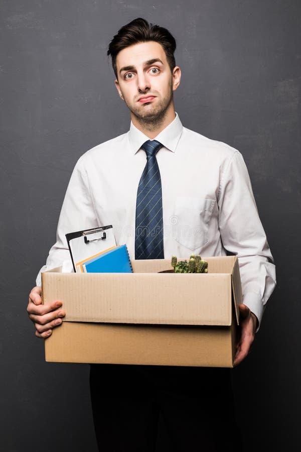 El conseguir encendido Hombre de negocios hermoso en el desgaste formal que sostiene una caja con su materia, en fondo gris imagen de archivo