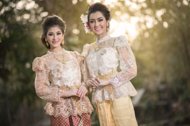 El conseguir hermoso de dos muchachas se vistió en traje tradicional tailandés imagen de archivo