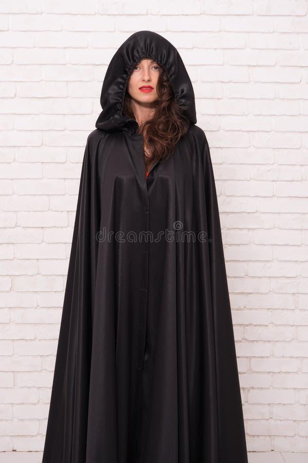 El conseguir listo para el partido del traje Chica marchosa en el brickwall blanco Mujer sensual que lleva la toga negra con mira imagen de archivo