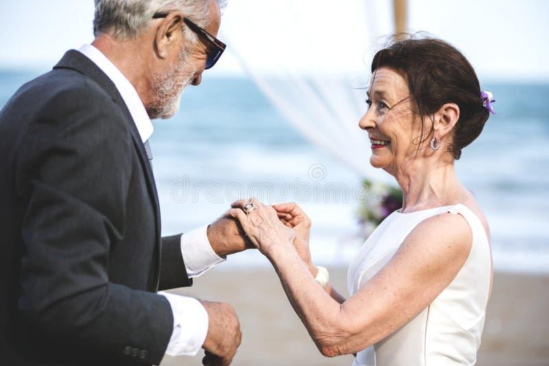 El conseguir maduro joven de la pareja se casó en la playa fotografía de archivo