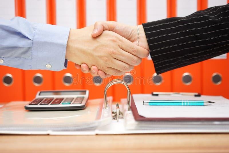 El consejero de impuesto es apretón de manos con el cliente satisfecho fotografía de archivo