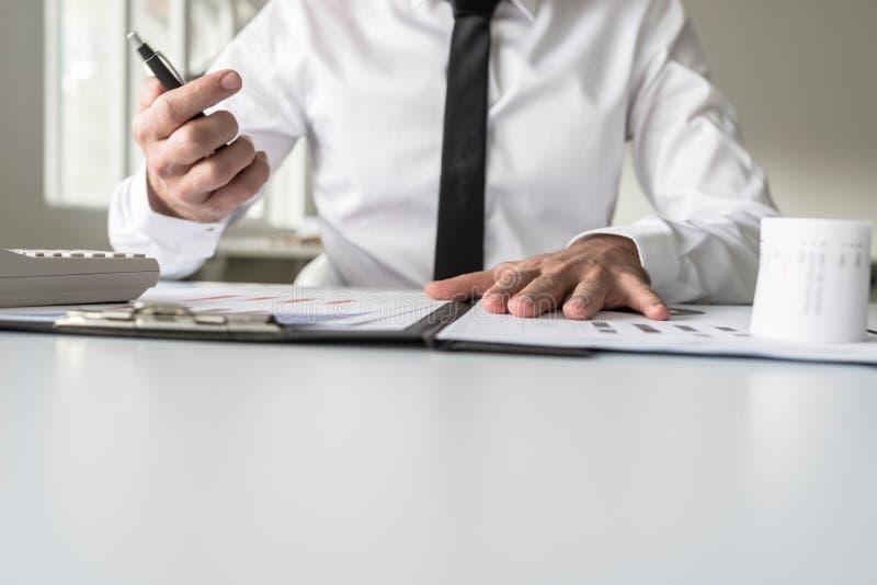 El consejero financiero ocupado que trabaja en su escritorio del negocio con muchos hace foto de archivo
