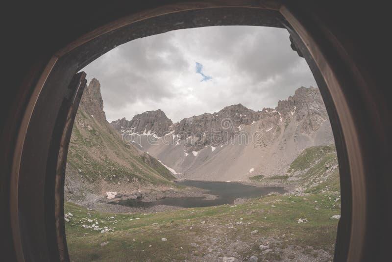 El considerar a través de ventana el panorama expansivo del valle alpino con el lago Aventuras y exploración del verano en las mo foto de archivo