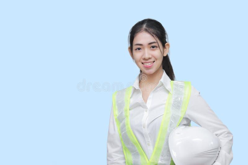 El constructor asiático sonriente de la mujer que presentaba en azul aisló el fondo imagen de archivo libre de regalías