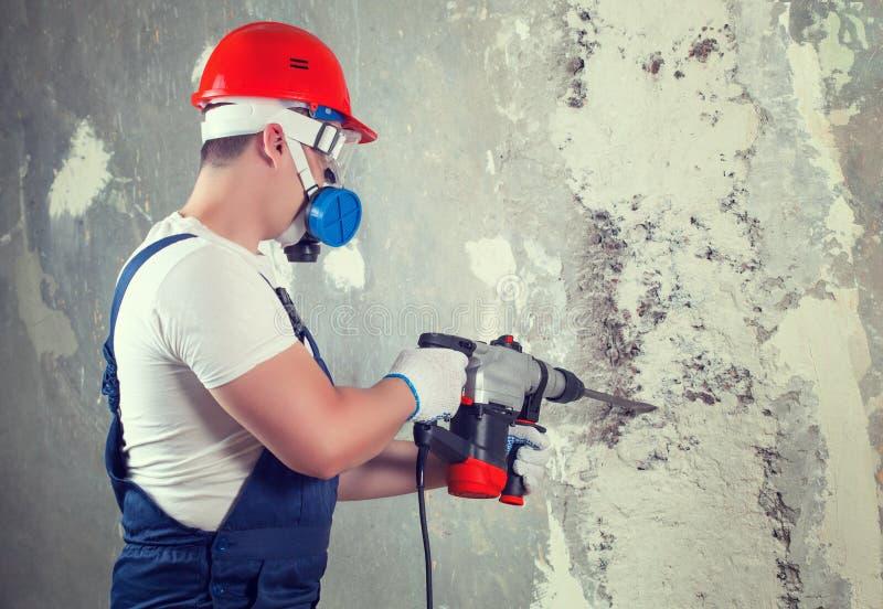 El constructor con el equipo del perforador del taladro de martillo que hace el agujero en pared fotografía de archivo libre de regalías