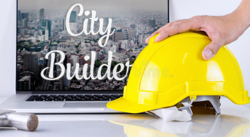 El constructor de la ciudad está cogiendo el casco de seguridad fotos de archivo libres de regalías