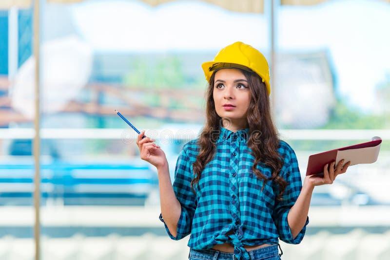 El constructor de la mujer que toma notas en el emplazamiento de la obra foto de archivo libre de regalías