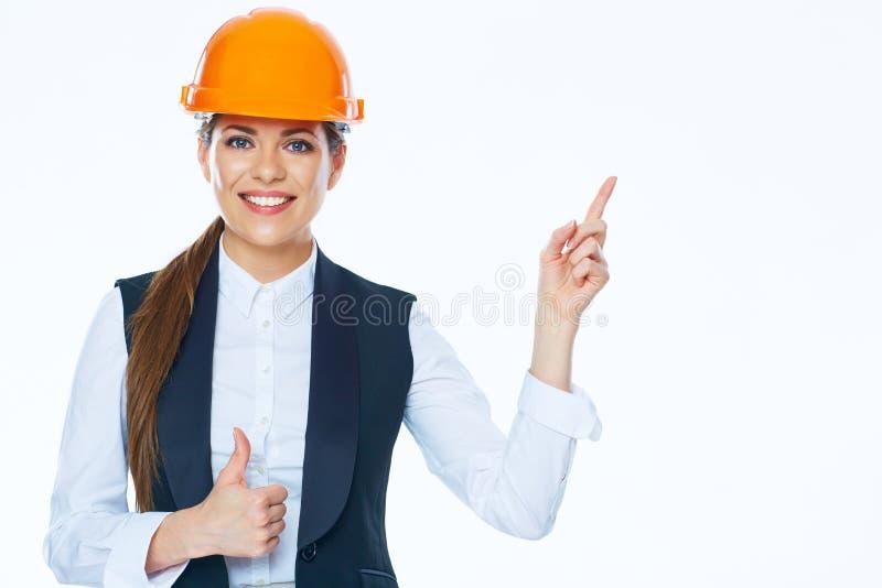 El constructor de la mujer señala el finger en espacio de la copia imagenes de archivo