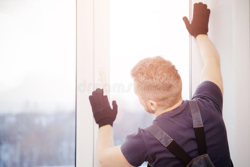 El constructor de sexo masculino instala y comprueba ventanas plásticas en edificio de apartamentos fotos de archivo libres de regalías