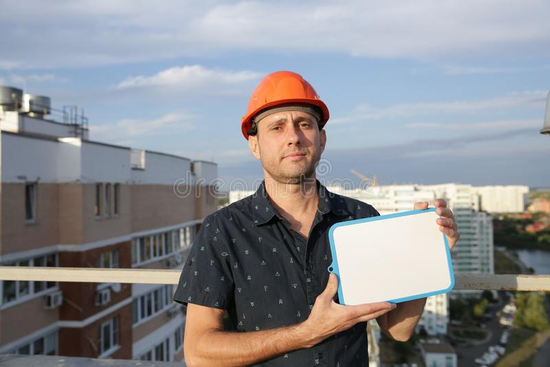 El constructor en un casco protector con una tableta para escribir en su mano se está colocando en el tejado de un edificio que p fotos de archivo libres de regalías