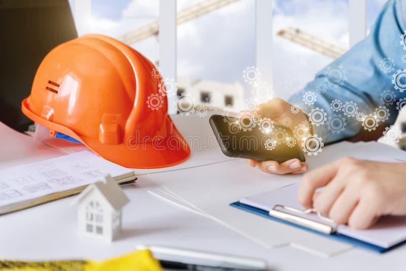 El constructor está trabajando en el teléfono en el escritorio imagen de archivo