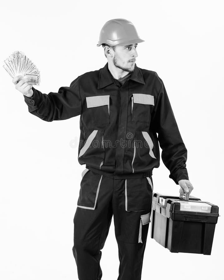 El constructor gana el dinero, reparador sostiene billetes de banco disponibles Concepto del día de paga El hombre con la caja de fotografía de archivo
