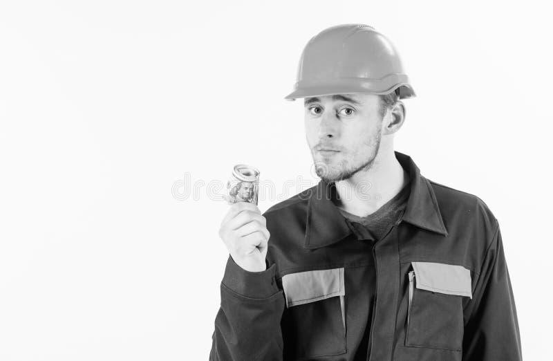 El constructor gana el dinero, reparador sostiene el efectivo, billetes de banco disponibles imagenes de archivo