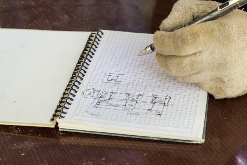 el constructor hace un dibujo de bosquejo de la casa La mano con una pluma dibuja foto de archivo