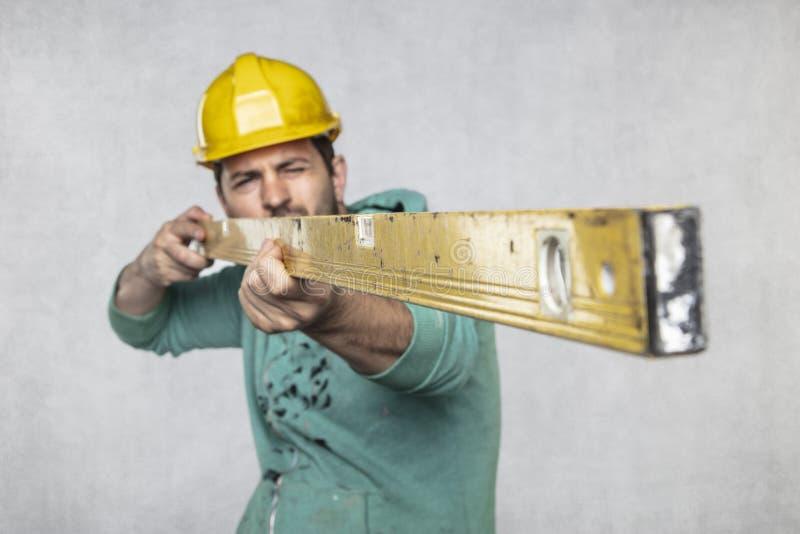 El constructor lleva a cabo en sus manos los niveles de alcohol, la idea de la exactitud en la construcción foto de archivo