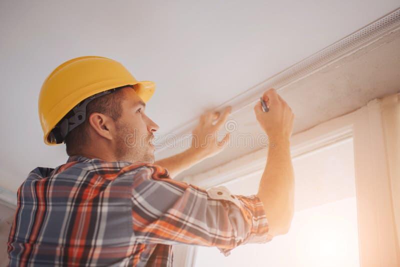 El constructor trabaja en el emplazamiento de la obra y mide el techo El trabajador en un casco anaranjado de la construcción hac imagen de archivo