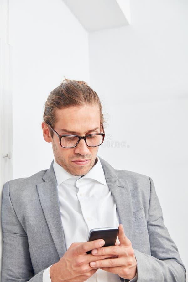 El consultor de negocio lee un mensaje de texto en el smartphone fotos de archivo libres de regalías