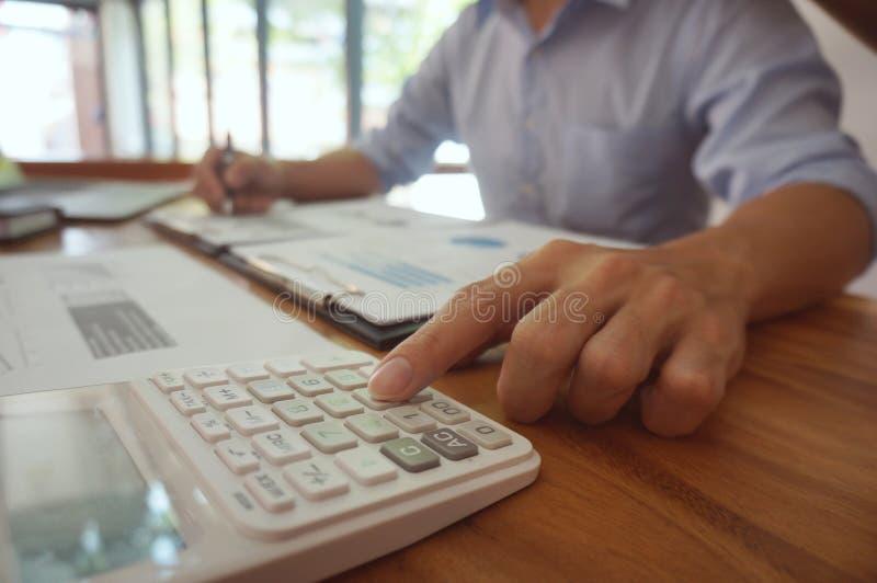 El contable verifica el dinero del negocio y del ahorro que apila el oro co fotografía de archivo