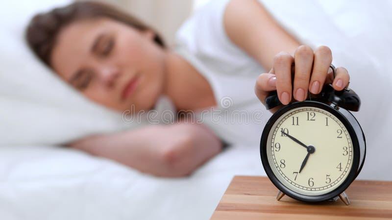 El contrario del despertador de la mujer joven soñolienta que estira la mano a querer de sonido de la alarma lo apaga Despierte t imagenes de archivo