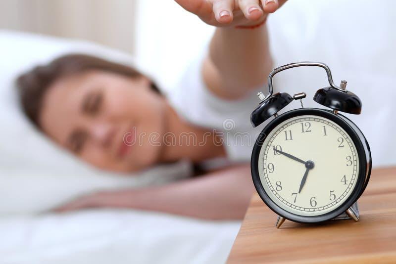El contrario del despertador de la mujer joven soñolienta que estira la mano a querer de sonido de la alarma lo apaga Despierte t foto de archivo libre de regalías