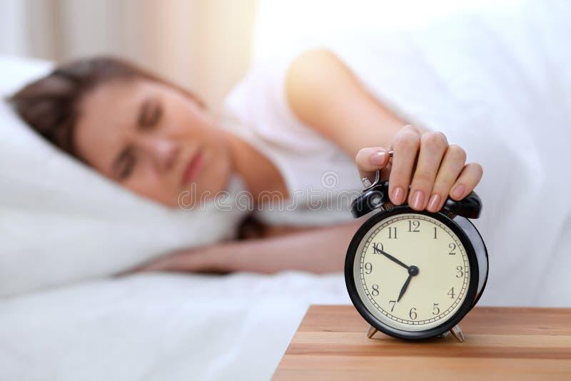 El contrario del despertador de la mujer joven soñolienta que estira la mano a querer de sonido de la alarma lo apaga Despierte t fotografía de archivo libre de regalías