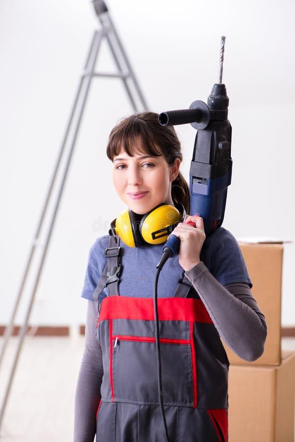 El contratista de la mujer con el taladro de mano en el emplazamiento de la obra imagen de archivo
