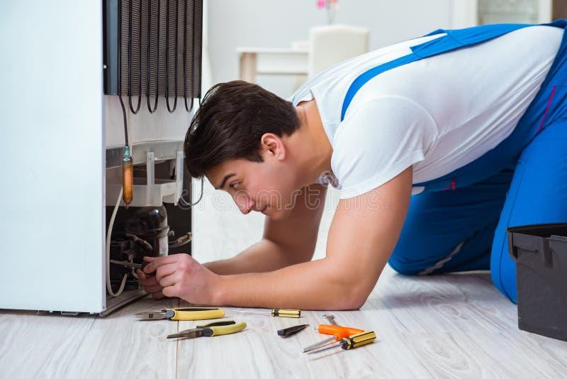 El contratista del reparador que repara el refrigerador en concepto diy imagen de archivo libre de regalías