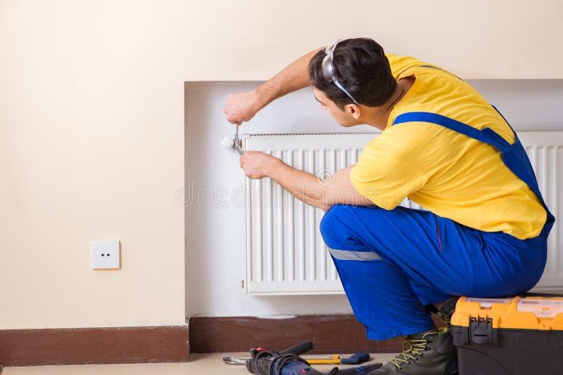 El contratista joven del reparador que repara el panel de la calefacción imagen de archivo