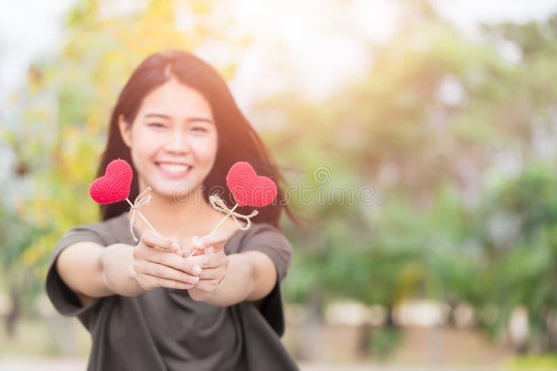 El control asiático de la mano de la mujer da el corazón rojo hermoso que el símbolo cariñoso dulce de toma cuidado fotos de archivo libres de regalías