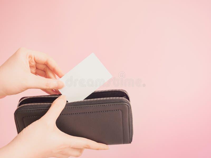 El control asiático de la mano de la mujer y pone en evidencia la tarjeta de crédito en sus purs azules imagenes de archivo