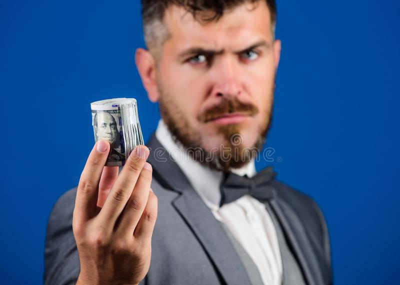 El control barbudo del inconformista del hombre rodó billetes de banco de los dólares Soborno o compra formal de la oferta del tr imagen de archivo