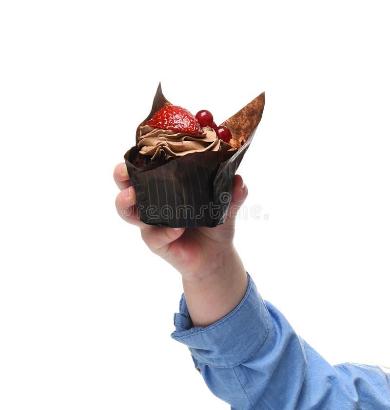 El control de la mano del bebé y da poca torta de chocolate del mollete con la fruta fresca de la fresa fotografía de archivo