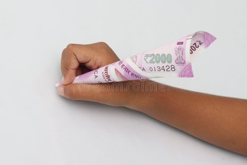 El control de la mano del ` s del niño 2000 notas de la rupia apenas le gusta una pluma fotos de archivo libres de regalías